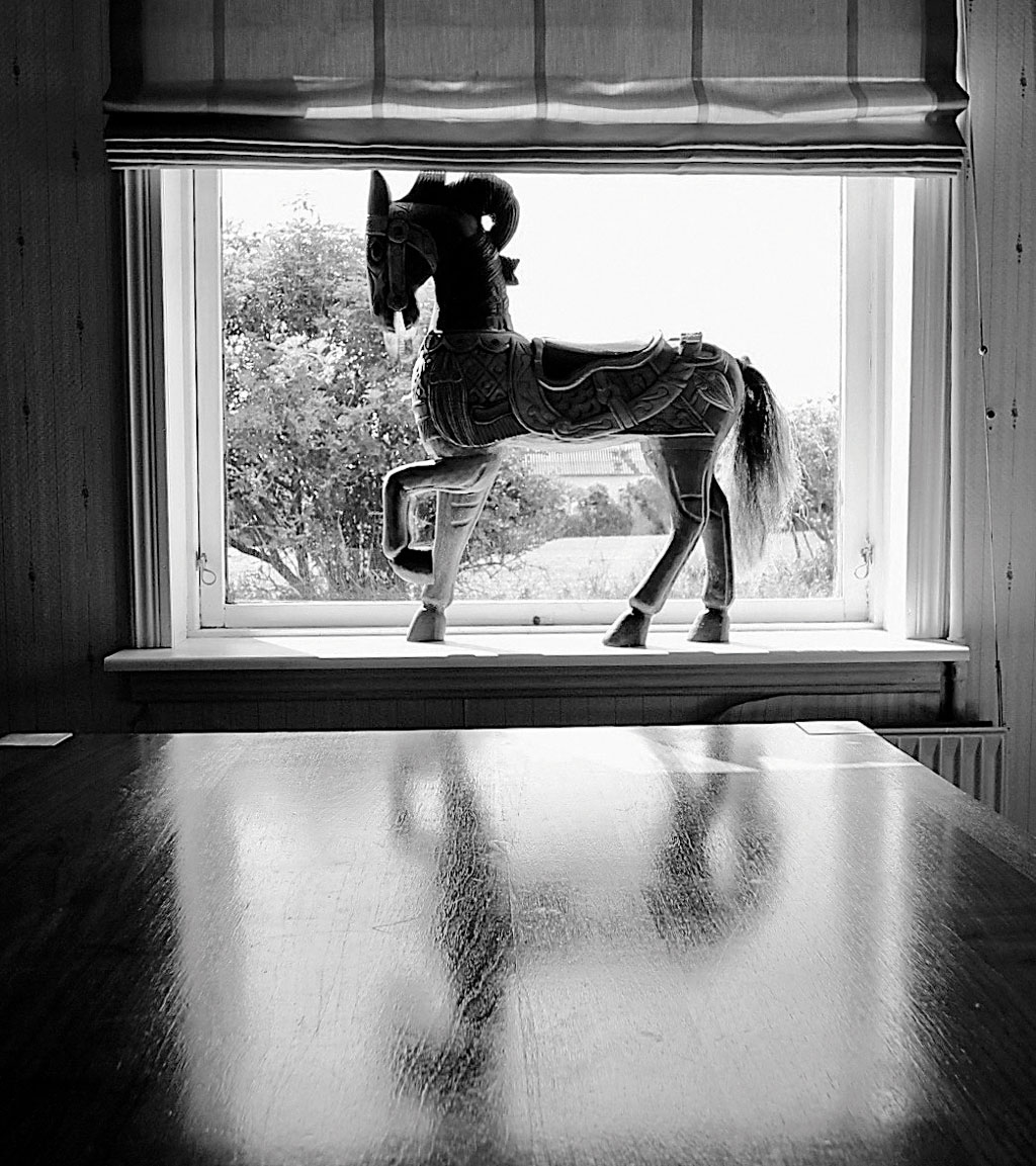 A wooden horse by the window in the cosy Finderup home in Denmark