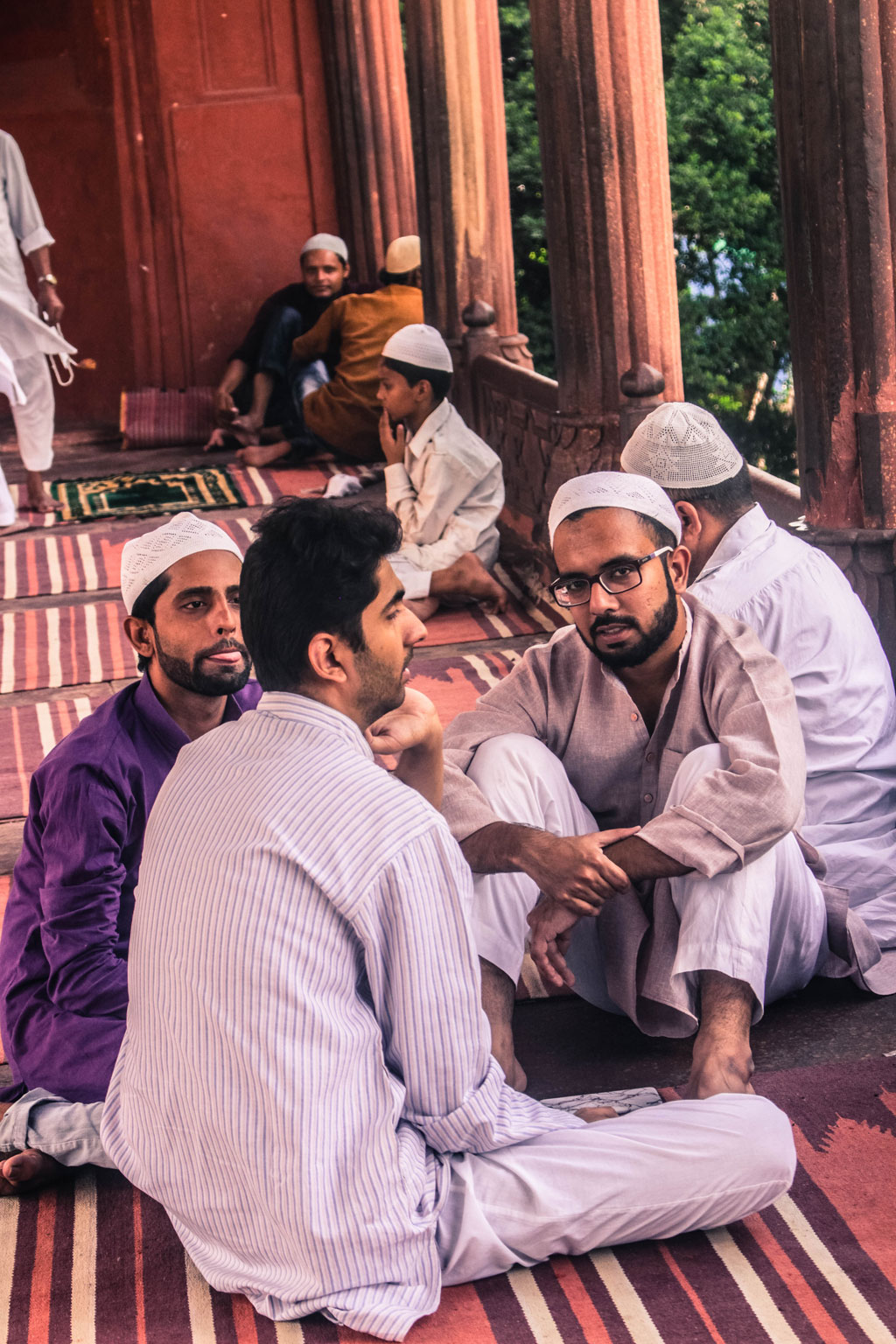 Individuals sit within the confines of the Jama Masjid to discuss daily affairs such as rising petrol prices after offering their prayers.