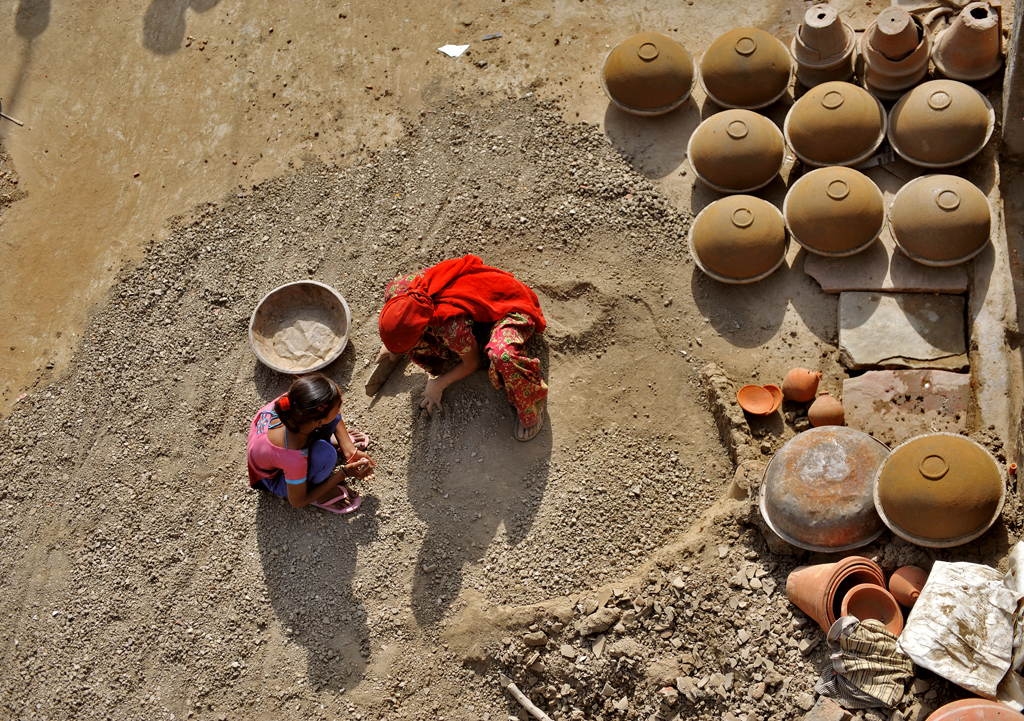 Women are given the task of breaking dried clay into fine powder